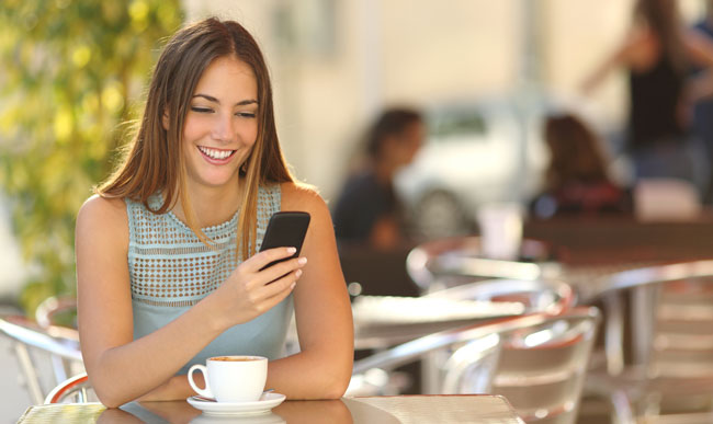 Girl with smart phone in a restaurant